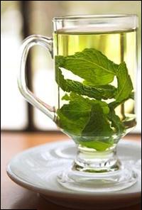 hot green tea in a clear glass mug